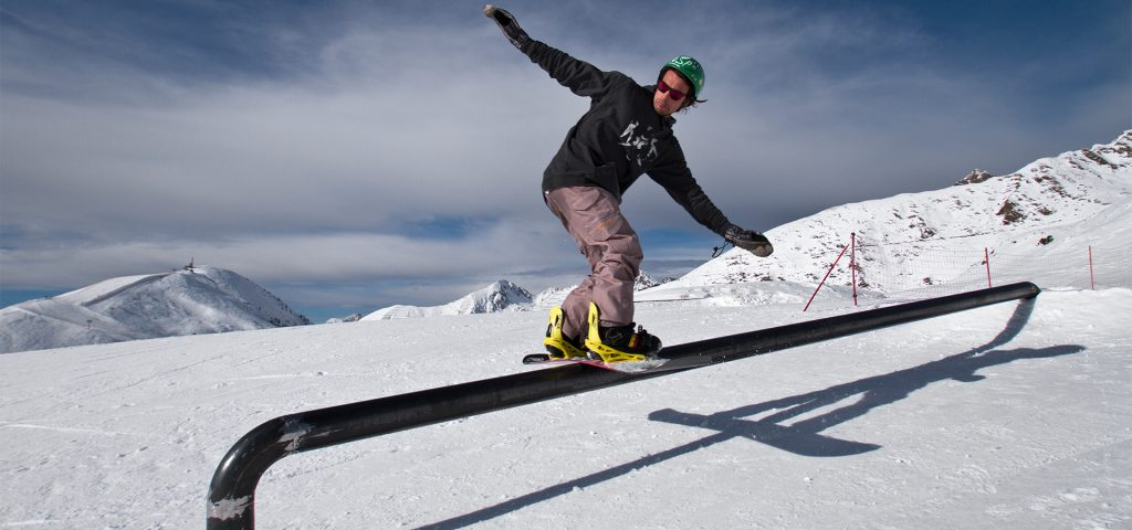 Man sliding on rail in snowboard park