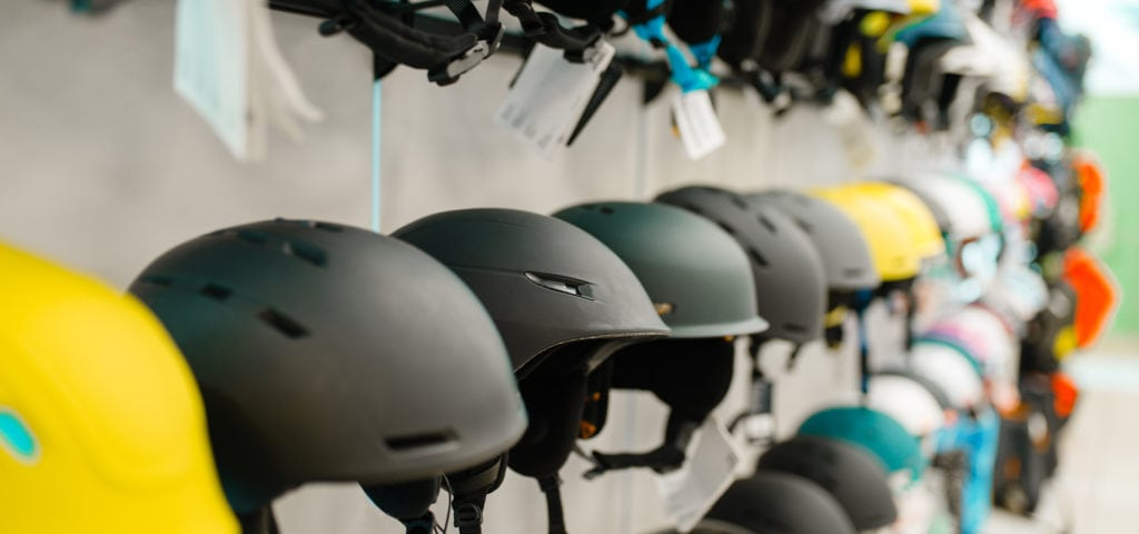 Rows of snowboard helmets in sports shop
