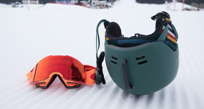 Ski helmet and goggles laying in the snow