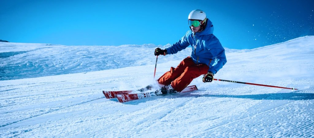 man going fast downhill on skis