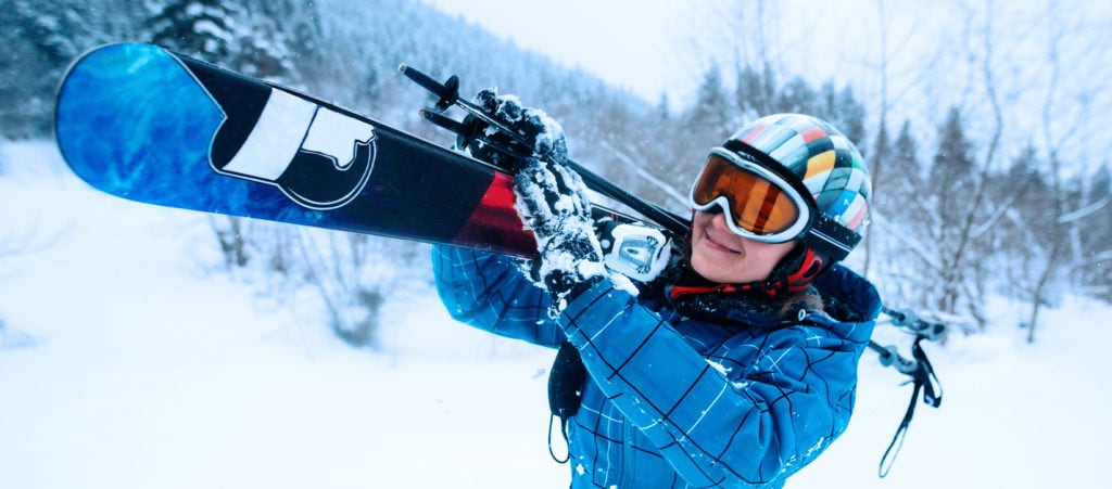 woman carrying her skis