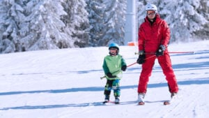 Ski instructor teaching a kid how to ski