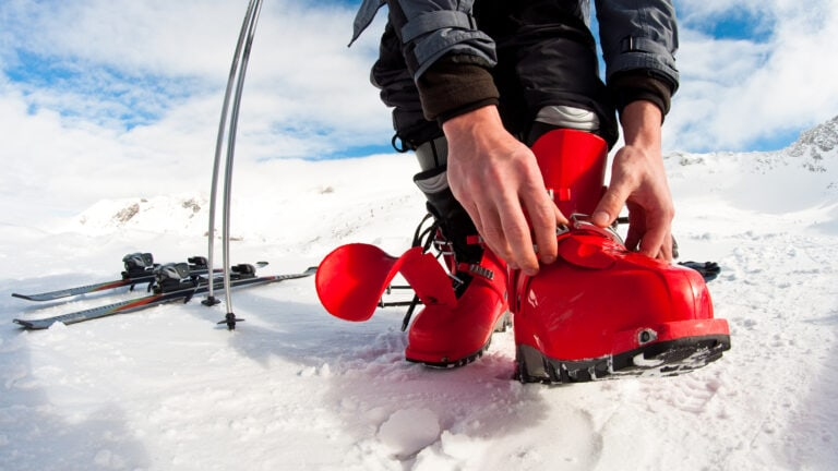 man fastening his ski boots before hitting the slope