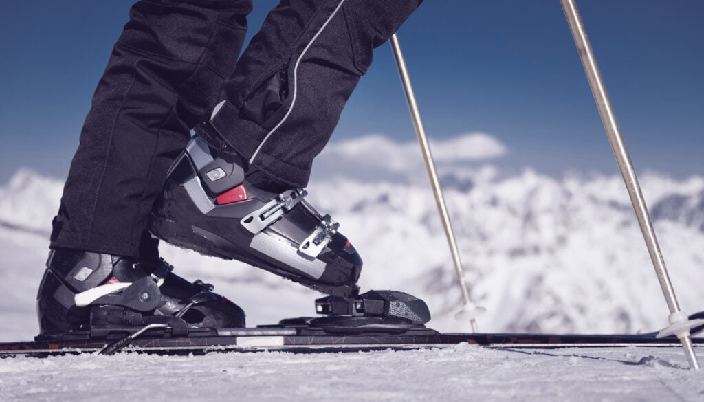 Closeup of skier clicking boots in his ski bindings