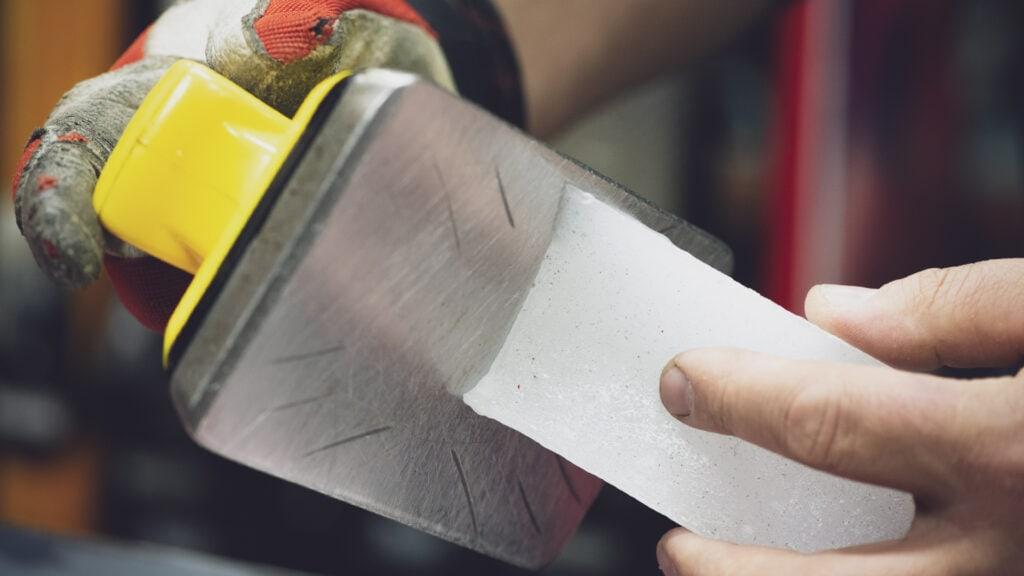 man applying wax to a snowboard waxing iron