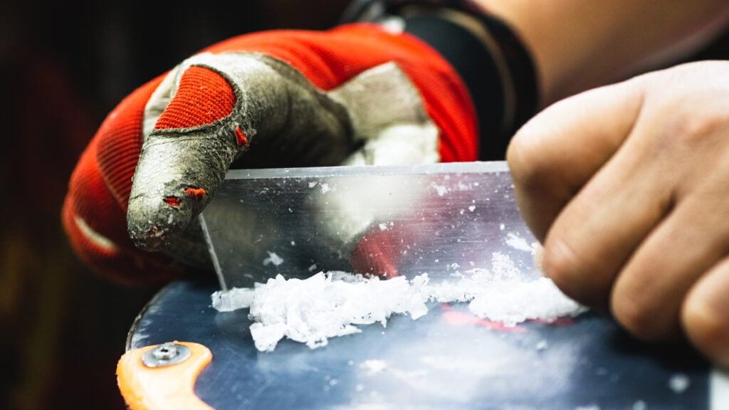 man scraping off wax on a snowboard using a snowboard scraper