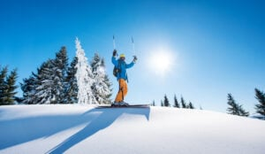 Low angle shot of a cheerful skier holding ski poles raising his arms in the air