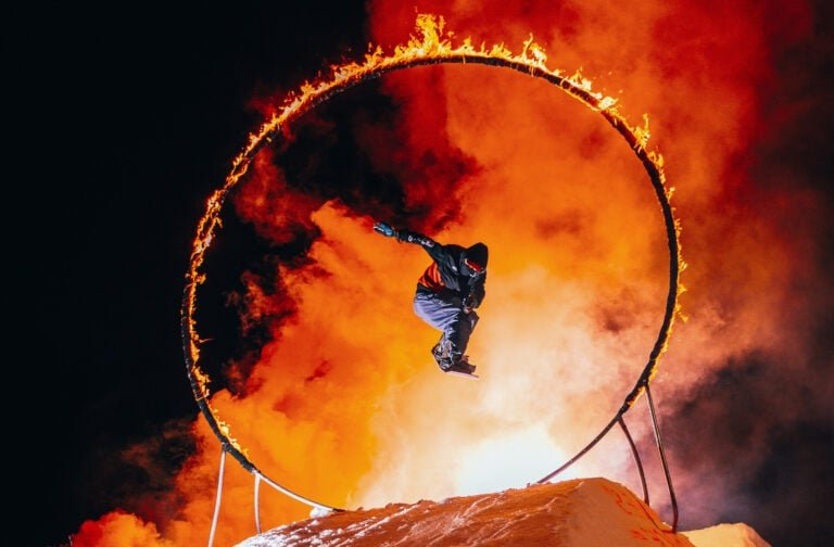 extreme showboarder jumping through a ring on fire