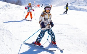young kids learning to alpine ski in a ski resort