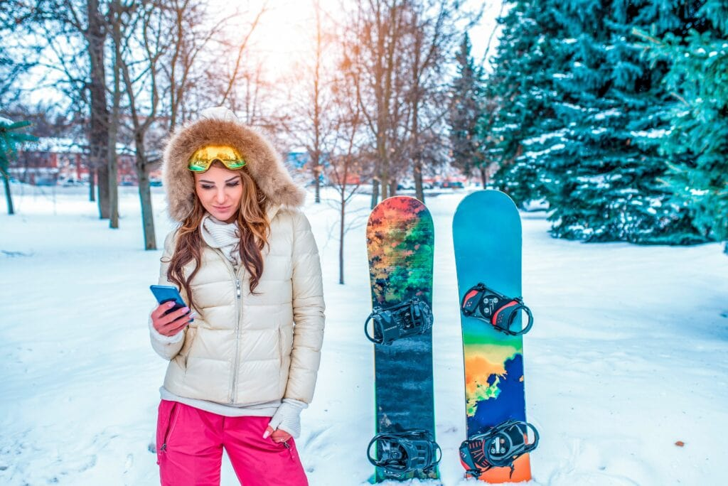 A girl with a phone is standing in the winter in the forest on the background of snowboard boards, in a warm jacket and pink pants. Online application in social networks chat correspondence.