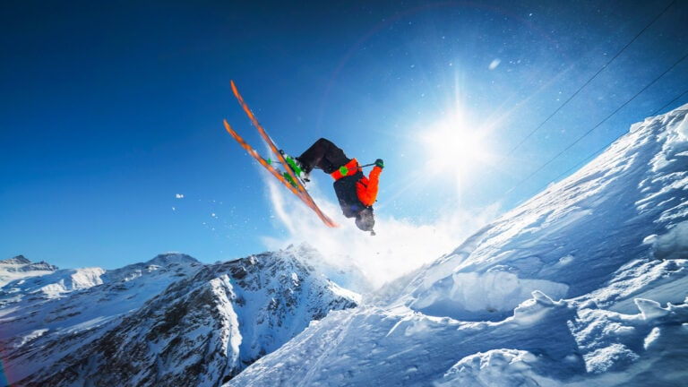 man doing a scenic backflip on his skis in the mountains