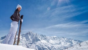 smiling woman with skis in her hands on top of a snowy mountain